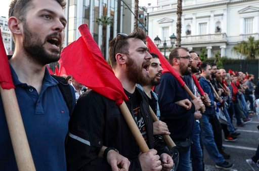 (AP Photo/Yorgos Karahalis). Supporters of the Greek Communist party chant slogans during an anti-war rally in Athens, Saturday, April 14, 2018. Thousands of supporters of the party marched to the U.S. embassy opposing the military strikes by western c...