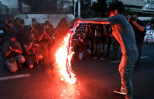(AP Photo/Yorgos Karahalis). A protester holds a burning U.S. flag during a rally outside the U.S. embassy in Athens, Saturday, April 14, 2018. Thousands of supporters of the Greek Communist party marched to the embassy during an anti-war rally opposin...