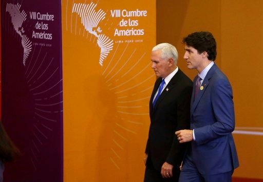 (AP Photo/Martin Mejia). U.S. Vice President Mike Pence, left, arrives with Canada's Prime Minister Justin Trudeau for the group photo at Americas Summit in Lima, Peru, Saturday, April 14, 2018.