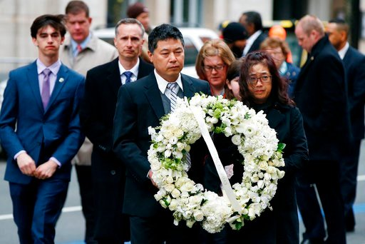 (AP Photo/Michael Dwyer). The father of Lingzi Lu, Jun Lu, foreground left, and her aunt Helen Zhao, foreground right, carry a wreath ahead of the family of Martin Richard, background from left, Henry, Bill, Denise and Jane, partially hidden, during a ...