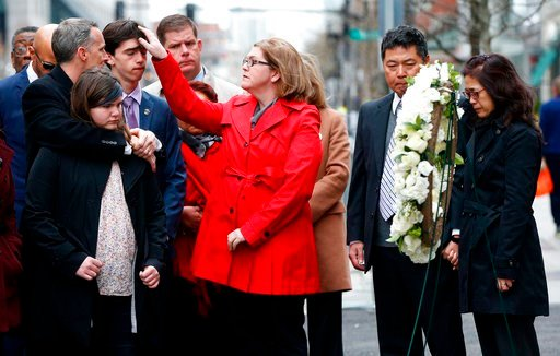 (AP Photo/Michael Dwyer). The father of Lingzi Lu, Jun Lu, second from right, and her aunt Helen Zhao, right, observe a moment of silence with the family of Martin Richard, foreground from left, Bill, Jane, Henry and Denise, during a ceremony at the si...