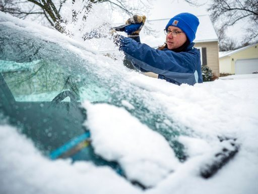 (Joe Ahlquist /The Rochester Post-Bulletin via AP). Colleen Streefland  brushes snow and ice of her vehicle during a storm Saturday, April 14, 2018, in Rochester, Minn.  A storm system stretching from the Gulf Coast to the Great Lakes buffeted the cent...