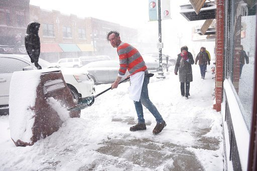 (Briana Sanchez /The Argus Leader via AP). M.B. Haskett cook Mark Romanowski shovels snow in front of the restaurant, Saturday, April 14, in Sioux Falls, S.D. M.B. Haskett was one of the few restaurants open downtown Saturday.