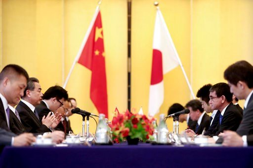 (Behrouz Mehri/Pool Photo via AP). Japanese Foreign Minister Taro Kono, second from right, and his Chinese counterpart Wang Yi, second from left, attend their meeting in Tokyo Sunday, April 15, 2018. Chinese Foreign Minister Wang starts two-day visit w...