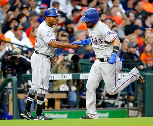 (AP Photo/Michael Wyke). Texas Rangers third base coach Steve Buechele, left, shakes hand with Robinson Chirinos after hitting a home run during the third inning of a baseball game against the Houston Astros Sunday, April 15, 2018, in Houston.