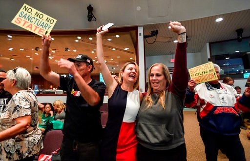 (Jeff Gritchen/The Orange County Register via AP, File). In this March 27, 2018, file photo, David Hernandez, left, Genevieve Peters, center, and Jennifer Martinez celebrate after the Orange County Board of Supervisors voted to join the U.S. Dep...