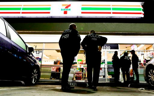 (AP Photo/Chris Carlson, File). In this Jan. 10, 2018, file photo, U.S. Immigration and Customs Enforcement agents serve an employment audit notice at a 7-Eleven convenience store in Los Angeles.