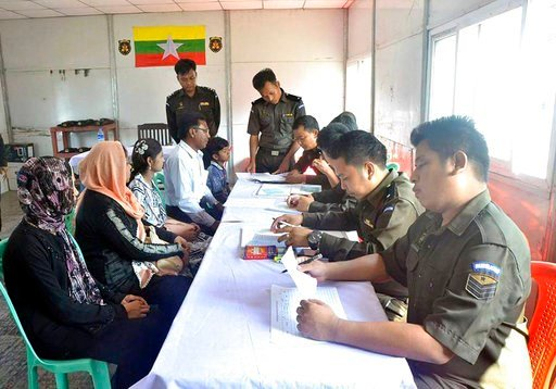 (Myanmar Government Information Committee via AP). In this April 14, 2018, photo provided by  Myanmar Government Information Committee,  Myanmar immigration officials examine documents as a Rohingya family of five look on at a receiving center in Taung...
