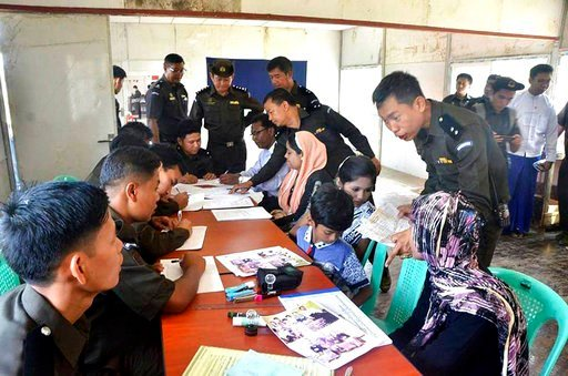 (Myanmar Government Information Committee via AP). In this April 14, 2018, photo provided by  Myanmar Government Information Committee, Myanmar immigration officials examine documents and photographs with a Rohingya family of five at a receiving center...
