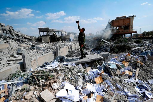 (AP Photo/Hassan Ammar, File). FILE - In this Saturday, April 14, 2018 file photo, a Syrian soldier films the damage of the Syrian Scientific Research Center which was attacked by U.S., British and French military strikes to punish President Bashar Ass...