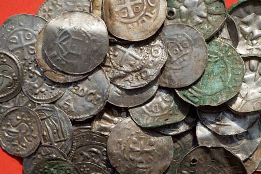 (Stefan Sauer/dpa via AP). The April 13, 2018 photo shows medieval Saxonian, Ottoman, Danish and Byzantine coins after a medieval silver treasure had been found near Schaprode on the northern German island of Ruegen in the Baltic Sea.