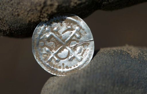 (Stefan Sauer/dpa via AP). In this April 13, 2018 photo an archeologist holds an ancient Danish coin which was minted under King Harald Bluetooth after a medieval silver treasure had been found near Schaprdoe on the northern German island of Ruegen in ...