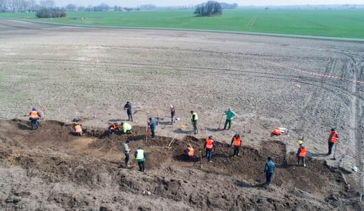 (Stefan Sauer/dpa via AP). In this April 13, 2018 photo archaeologists search for coins and jewelry after a medieval silver treasure had been found near Schaprode on the northern German island of Ruegen in the Baltic Sea.