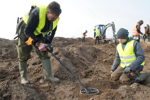 (Stefan Sauer/dpa via AP). In this April 13, 2018 photo hobby archaeologist Rene Schoen and 13-year-old  Luca Malaschnitschenko, right, search for coins after a medieval silver treasure had been found near Schaprode on the northern German island of Rue...