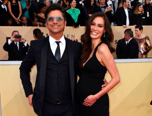 (Photo by Jordan Strauss/Invision/AP, File). FILE - In this Jan. 21, 2018, file photo, John Stamos, left, and Caitlin McHugh arrive at the 24th annual Screen Actors Guild Awards at the Shrine Auditorium & Expo Hall in Los Angeles. Stamos announced ...