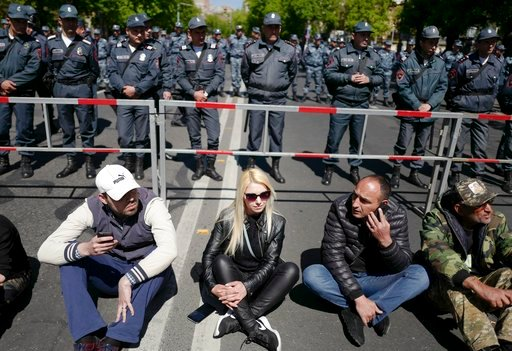 (Vahan Stepanyan, PAN Photo via AP). Opposition demonstrators sit in front of police line to protest the former president's shift into the prime minister's seat in Yerevan, Armenia, Monday, April 16, 2018. Thousands of opposition supporters have blocke...