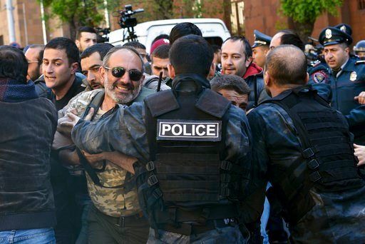 (Karo Sahakyan, PAN Photo via AP). Police officers restrain opposition demonstrators as they march to protest the former president's shift into the prime minister's seat in Yerevan, Armenia, Monday, April 16, 2018. Thousands of opposition supporters ha...