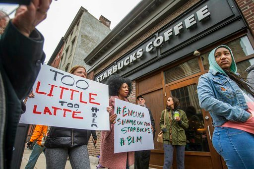 (Michael Bryant/The Philadelphia Inquirer via AP). Protesters gather outside of a  Starbucks in Philadelphia, Sunday, April 15, 2018, where two black men were arrested Thursday after employees called police to say the men were trespassing. The arrest p...