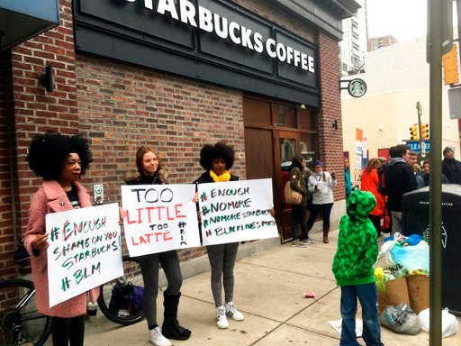 (AP Photo/Ron Todt). Protesters gather outside a Starbucks in Philadelphia, Sunday, April 15, 2018, where two black men were arrested Thursday after Starbucks employees called police to say the men were trespassing. The arrest prompted accusations of r...