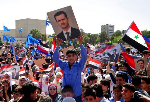 (SANA via AP). In this photo released by the Syrian official news agency SANA, protesters wave flags and portraits of President Bashar Assad, as they march during a demonstration to show solidarity with the Syrian armed forces, at Omayyad Square, in Da...