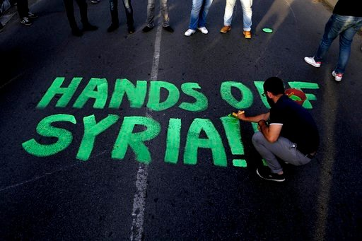 "(AP Photo/Petros Karadjias). A protestor paints ""Hands off Syria"" on the street during a protest against the airstrikes on suspected chemical weapons sites in Syria, outside of the U.S embassy in capital Nicosia, Cyprus, Monday, April 16, 2018. Hundred..."