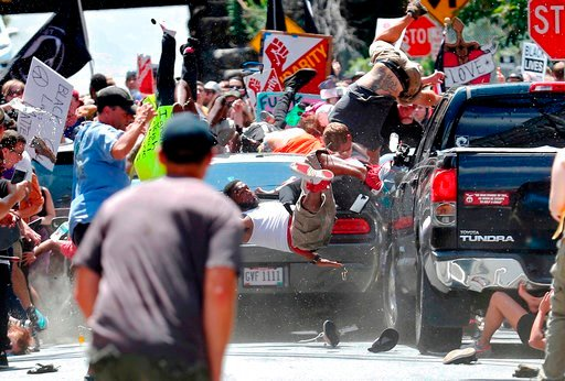 (Ryan Kelly/The Daily Progress via AP). In this Aug. 12, 2017, photo by Ryan Kelly of The Daily Progress, people fly into the air as a car drives into a group of protesters demonstrating against a white nationalist rally in Charlottesville, Va. The pho...