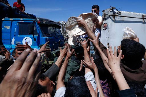 (AP Photo/Hassan Ammar). Syrian authorities distribute bread, vegetables and pasta to Douma residents, in the town of Douma, the site of a suspected chemical weapons attack, near Damascus, Syria, Monday, April 16, 2018. Two days after Syrian troops dec...