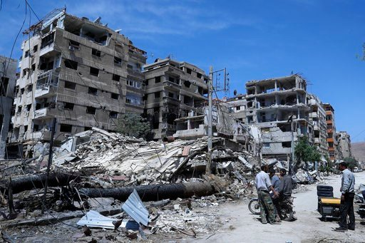 (AP Photo/Hassan Ammar). People stand in front of damaged buildings, in the town of Douma, the site of a suspected chemical weapons attack, near Damascus, Syria, Monday, April 16, 2018. Two days after Syrian troops declared Douma liberated from opposit...