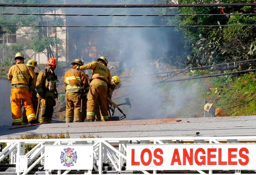 (AP Photo/Damian Dovarganes). Los Angeles firefighrers knock down hot spots on the roof of a music studio in Los Angeles Saturday, April 14, 2018. Officials says two people were killed and at least three others were hurt when flames ripped through the ...