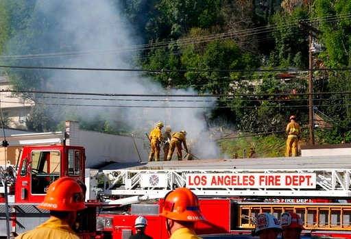 (AP Photo/Damian Dovarganes). Los Angeles firefighters knock down hot spots on the roof of a music studio in Los Angeles Saturday, April. 14, 2018. Officials says two people were killed and at least three others were hurt when flames ripped through the...