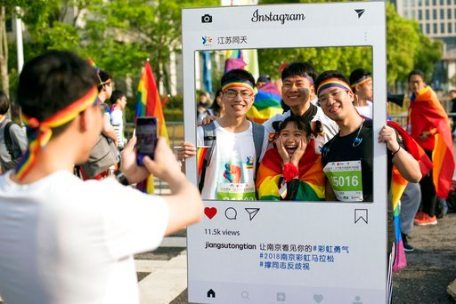 """(Jiangsu Tongtian Volunteer Group via AP). In this April 15, 2018 photo released by Jiangsu Tongtian Volunteer Group, participants pose for photos during a """"Rainbow Marathon,"""" organized months earlier, to raise awareness of LGBT issues in Nanjing in ea..."""