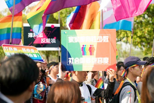 """(Jiangsu Tongtian Volunteer Group via AP). In this April 15, 2018 photo released by Jiangsu Tongtian Volunteer Group, a participant holds a sign which reads """"Every family has sexual minority, society needs more tolerance"""" during a """"Rainbow Marathon,"""" o..."""
