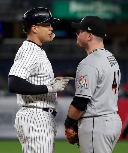 (AP Photo/Julie Jacobson). New York Yankees' Giancarlo Stanton, left, speaks with Miami Marlins first baseman Justin Bour (41) after walking during the fourth inning of a baseball game, Monday, April 16, 2018, in New York.