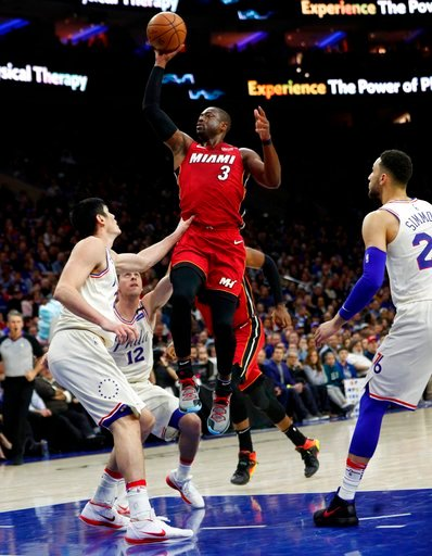 (AP Photo/Chris Szagola). Miami Heat's Dwyane Wade, right, shoots with Philadelphia 76ers' T.J. McConnell, center, and Ersan Ilyasova, left, of Turkey, defend during the first half in Game 2 of a first-round NBA basketball playoff series, Monday, April...