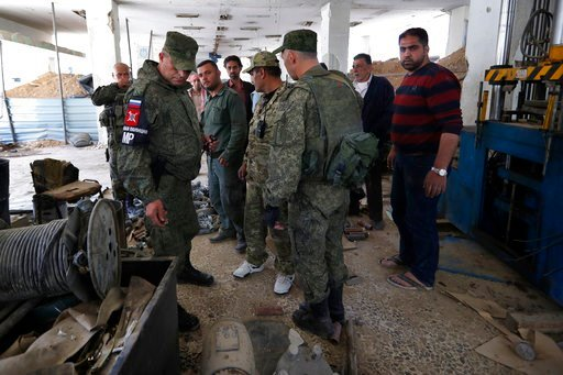 (AP Photo/Hassan Ammar). Russian military police officers check weapons left behind by members of the Army of Islam group in a factory produced weapons, in the town of Douma, the site of a suspected chemical weapons attack, near Damascus, Syria.