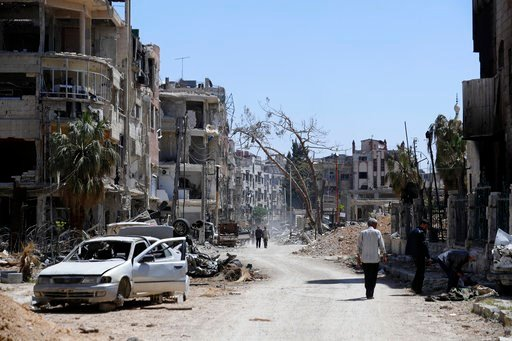 (AP Photo/Hassan Ammar). Syrians walk through destruction in the town of Douma, the site of a suspected chemical weapons attack, near Damascus, Syria, Monday, April 16, 2018.