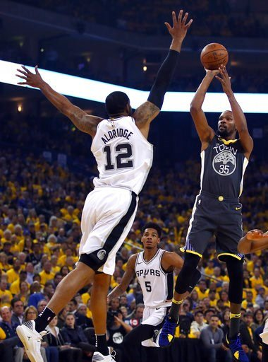 (AP Photo/Ben Margot). Golden State Warriors' Kevin Durant, right, shoots against San Antonio Spurs' LaMarcus Aldridge (12) during the first quarter in Game 2 of a first-round NBA basketball playoff series Monday, April 16, 2018, in Oakland, Calif.