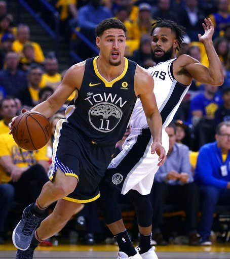 (AP Photo/Ben Margot). Golden State Warriors' Klay Thompson (11) drives the ball away from San Antonio Spurs' Patty Mills, right, during the first quarter in Game 2 of a first-round NBA basketball playoff series Monday, April 16, 2018, in Oakland, Calif.