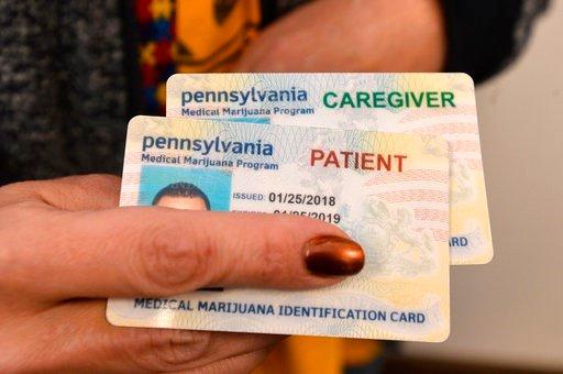 (Christopher Millette/Erie Times-News via AP). A caregiver shows what a medical marijuana identification card looks like for a caregiver and patient during an open house in Erie, Pa., Monday, April 16, 2018.