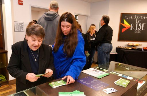 (Christopher Millette/Erie Times-News via AP). Diane Walters, left, and her caregiver Tasha Zirkle look over free literature during an open house in Erie, Pa., Monday, April 16, 2018, at the region's first medical marijuana dispensary.