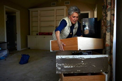 (AP Photo/Jae C. Hong). In this Wednesday, April 11, 2018, photo, mudslide survivor Mari Mitchel moves drawers covered in mud in her bedroom, in Montecito, Calif. The mudslide carried away everything from massive pieces of antique family furniture to a...