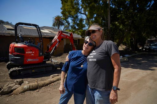 (AP Photo/Jae C. Hong). In this Wednesday, April 11, 2018, photo, mudslide survivor Mari Mitchel, left, is hugged by contractor Ann Burgard, who found Mitchel's jewelry, outside her home that was heavily damaged by mudslides, in Montecito, Calif. The m...