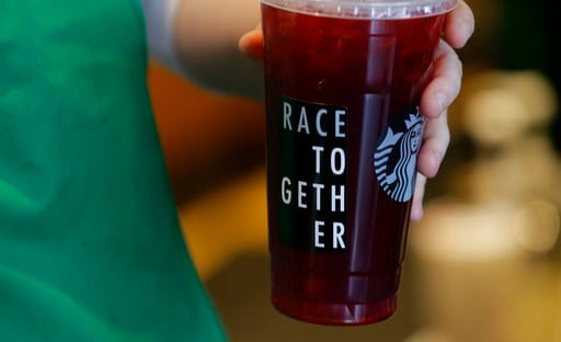 """(AP Photo/Ted S. Warren, File). In this March 18, 2015, file photo, a Starbucks barista holds an iced tea drink with a """"Race Together"""" sticker on it at a Starbucks store in Seattle."""