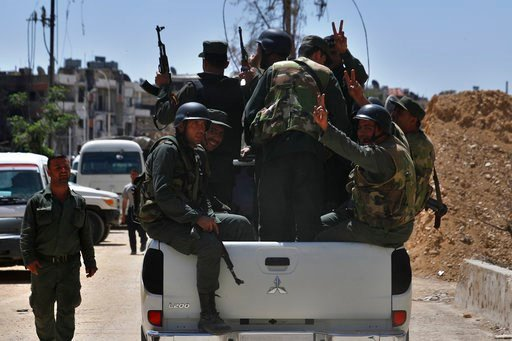 (AP Photo/Hassan Ammar). Syrian police units wave and give the victory sign as they patrol in the town of Douma, the site of a suspected chemical weapons attack, near Damascus, Syria, Monday, April 16, 2018. Faisal Mekdad, Syria's deputy foreign minist...
