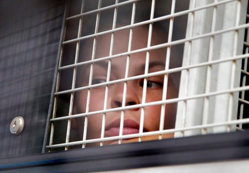 (AP Photo/Gemunu Amarasinghe). Anastasia Vashukevich sits inside a prison transport vehicle outside a courthouse in Pattaya, south of Bangkok, Thailand, Tuesday, April 17, 2018.  Russian sex guru and his followers, one of whom claims to have evidence o...