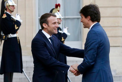 (AP Photo/Michel Euler). French President Emmanuel Macron, left, welcomes Canadian Prime Minister Justin Trudeau on the occasion of their meeting at the Elysee Palace in Paris, Monday, April 16, 2018. Trudeau is in France for a two-day visit.