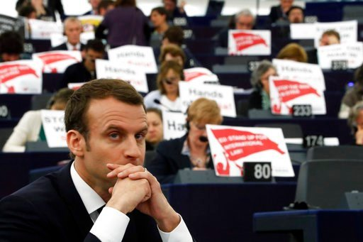 "(AP Photo/ Jean Francois Badias). French President Emmanuel Macron listens to speeches at the European Parliament in Strasbourg, eastern France, Tuesday, April 17, 2018 as European lawmakers raise placards reading ""Stop the War in Syria"" in protest aga..."