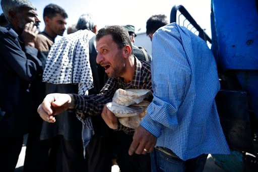 (AP Photo/Hassan Ammar). A Syrian man holds bread as Syrian authorities distributed bread, vegetables and pasta to Douma residents, in the town of Douma, the site of a suspected chemical weapons attack, near Damascus, Syria, Monday, April 16, 2018. Two...
