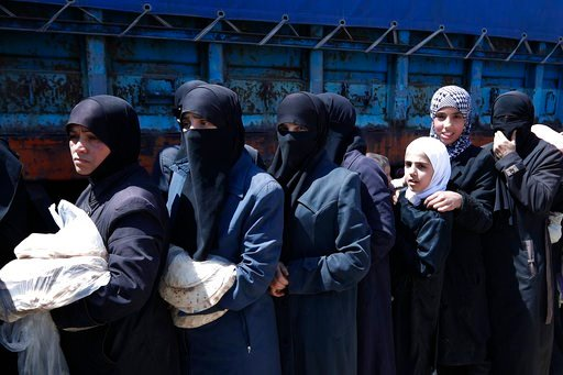 (AP Photo/Hassan Ammar). Syrian women wait for Syrian authorities distributing bread, vegetables and pasta to Douma residents, in the town of Douma, the site of a suspected chemical weapons attack, near Damascus, Syria, Monday, April 16, 2018. Two days...