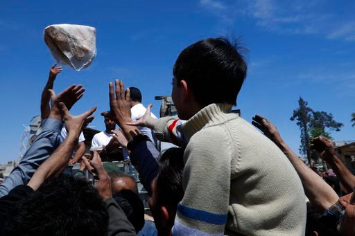(AP Photo/Hassan Ammar). Syrian authorities distribute bread, vegetables and pasta to residents in the town of Douma, the site of a suspected chemical weapons attack, near Damascus, Syria, Monday, April 16, 2018. Two days after Syrian troops declared D...
